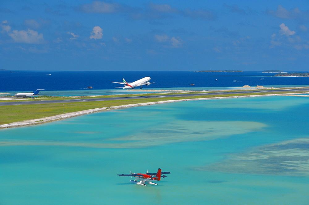 Passenger jet taking off from Male International Airport, and Maldivian air taxi ready to take off, Maldives, Indian Ocean, Asia