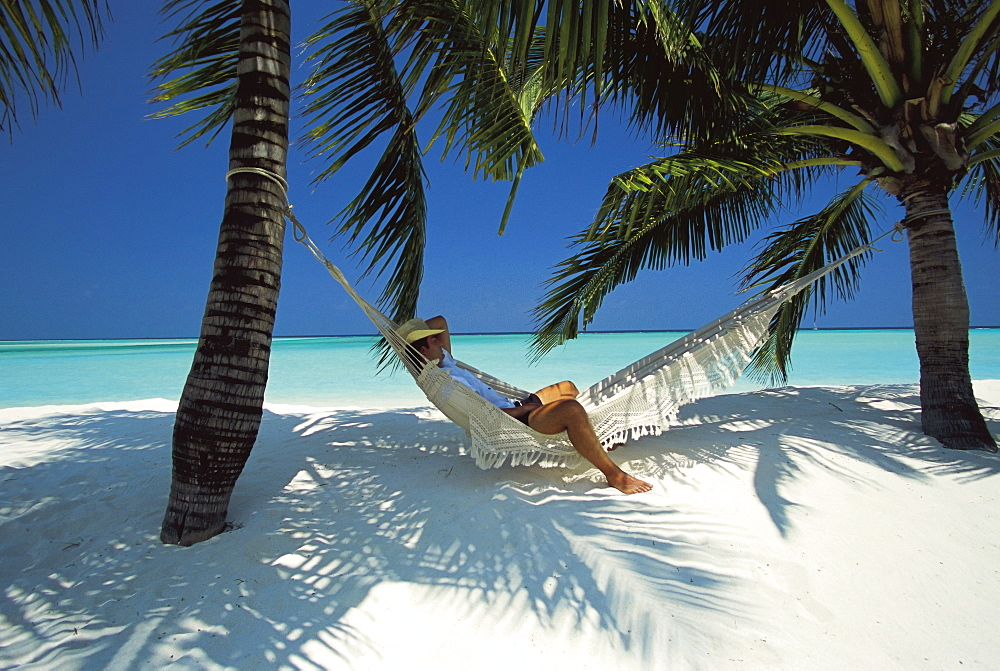 Man relaxing on a beachside hammock, Maldives, Indian Ocean, Asia - 795-141