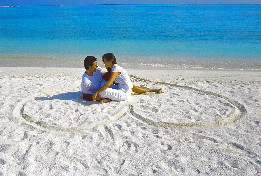 Young couple on beach sitting in a heart shaped imprint on the sand, Maldives, Indian Ocean, Asia - 795-210
