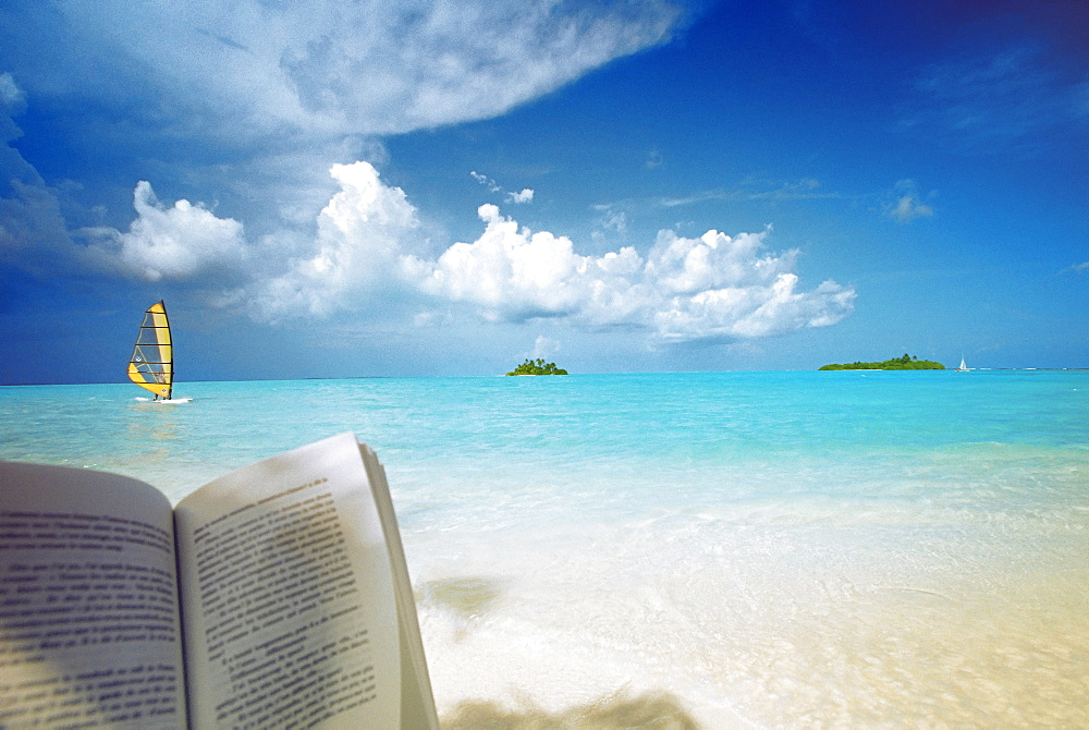 Reading book on the beach, windsurfing and islands in the distance, the Maldives, Indian Ocean - 795-235