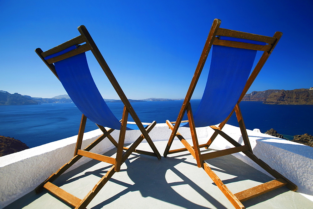 Deck chairs on terrace overlooking ocean, Santorini, Cyclades, Greek Islands, Greece, Europe - 795-421