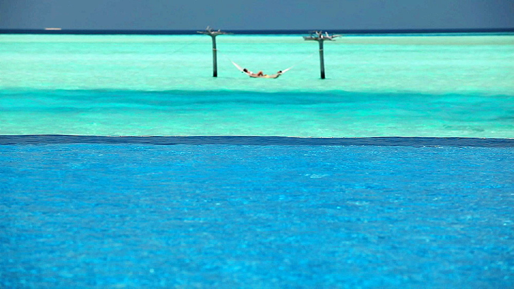 Couple in ocean hammock beyond swimming pool, Maldives, Indian Ocean