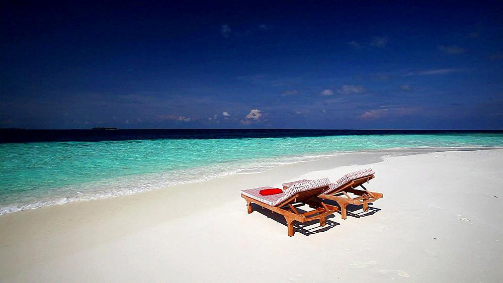 Deck chairs on tropical beach, Maldives, Indian Ocean