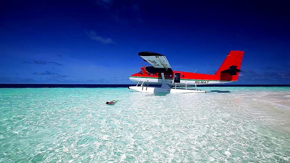 Airplane and woman snorkelling in the Maldives, Indian Ocean  - 795-503