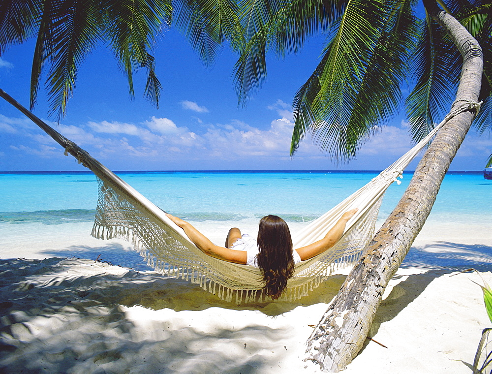 Woman sitting in hammock on beach, Maldives, Indian Ocean, Asia - 795-60