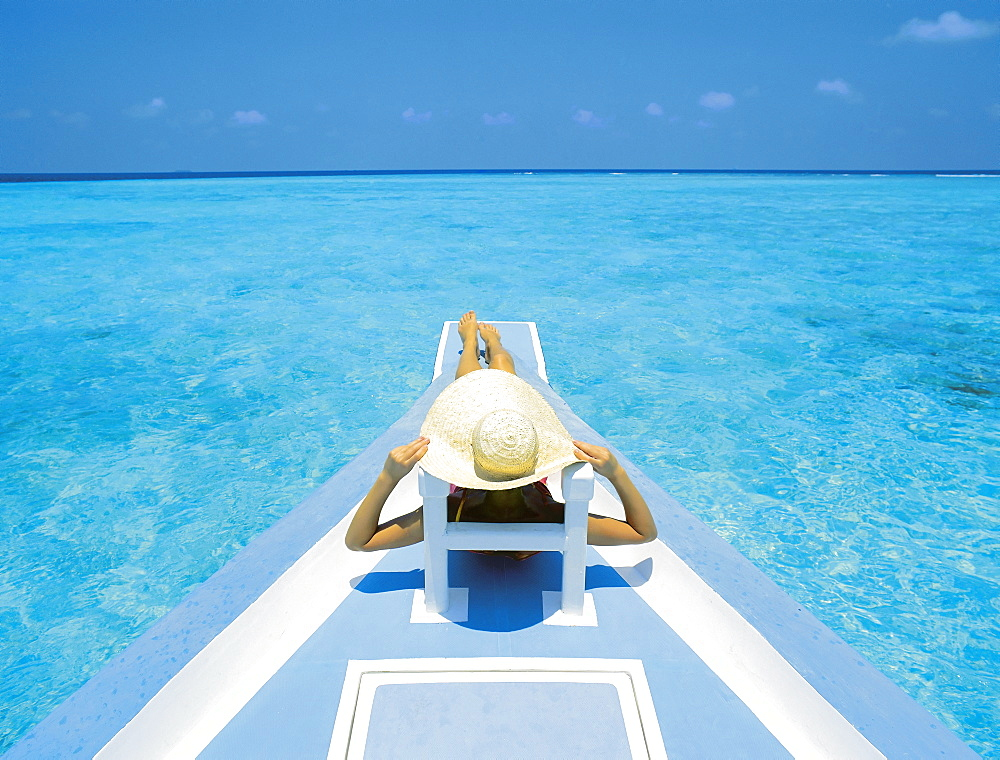 Woman relaxing on deck of boat, Maldives, Indian Ocean, Asia