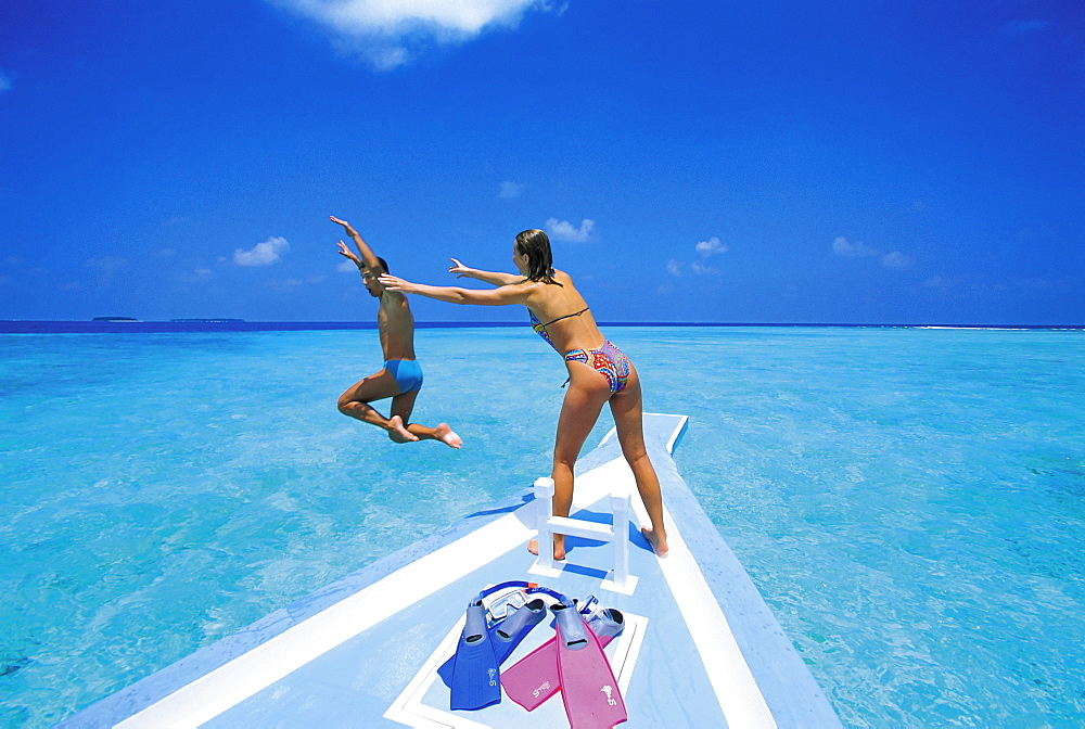 Couple at front of boat, man jumping in water, Maldives, Indian Ocean, Asia - 795-83