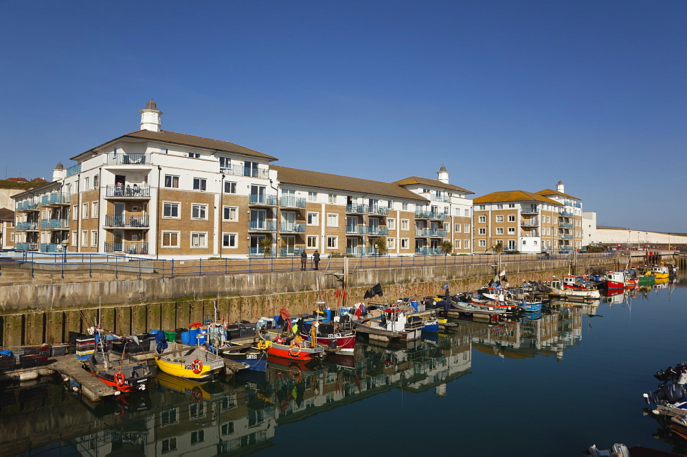 England, East Sussex, Brighton, view over fishing boats moored in the Marina with apartment buildings behind.