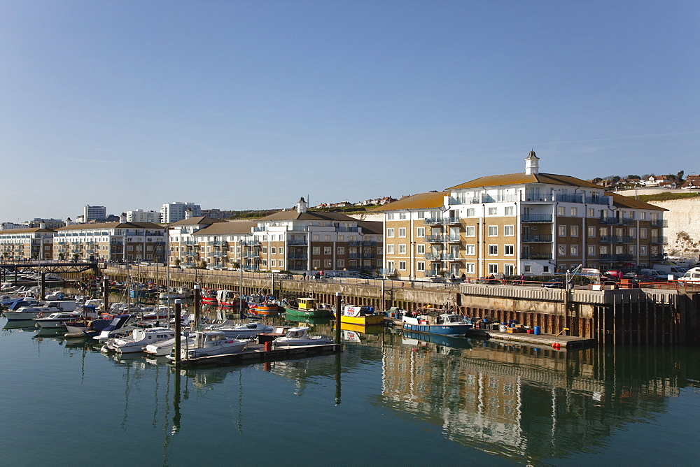 England, East Sussex, Brighton, view over boats moored in the Marina with apartment buildings behind.
