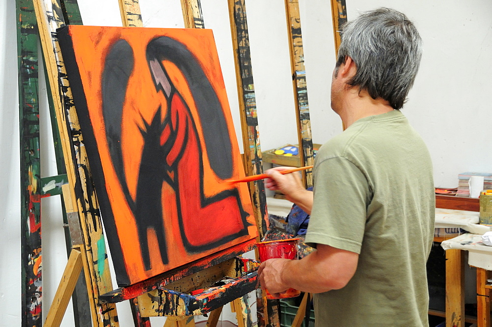 Mexico, Bajio, San Miguel de Allende, Artist Juan Ezcurdia in his studio working on painting at easel.