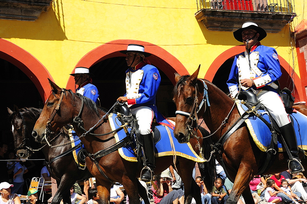 Mexico, Bajio, San Miguel de Allende, Independence Day celebrations. Re-enactment of the Call for Independence horsemen ride through street with watching crowd.