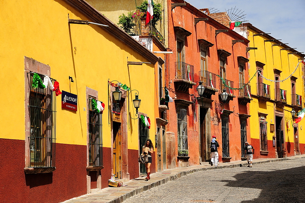 Mexico, Bajio, San Miguel de Allende, Independence Day decorations adorn colonial streets lined by brightly painted buildings.