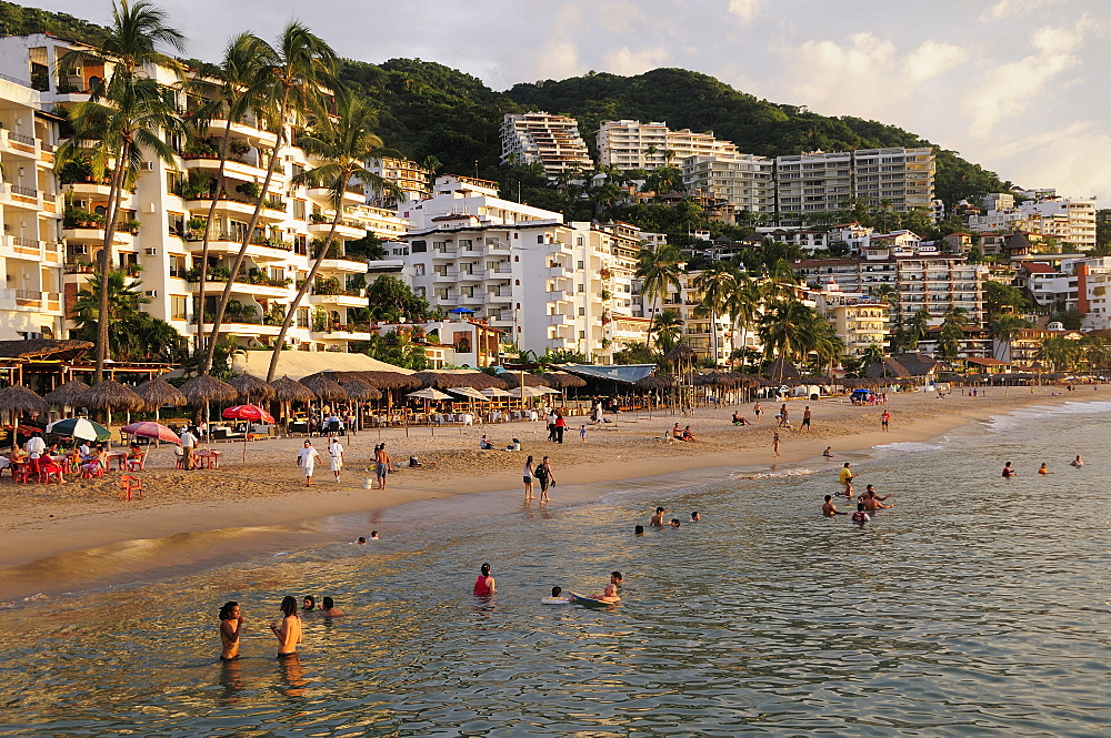 Mexico, Jalisco, Puerto Vallarta, View of Playa Los Muertos beach overlooked by hotels and apartments and lined with bars cafes and beach shades. People on beach and in the water.