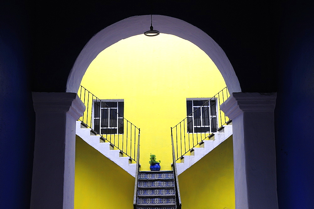 Mexico, Puebla, Looking into inner courtyard through archway in shadow towards yellow painted wall with blue and white tiled steps plant in blue pot and pair of square recessed windows.