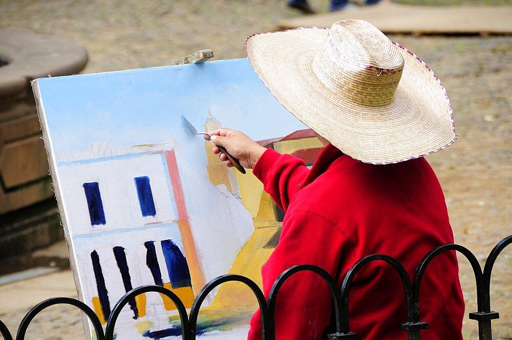 Mexico, Michoacan, Patzcuaro, Painter in Plaza Vasco de Quiroga applying paint to canvas using palette knife.
