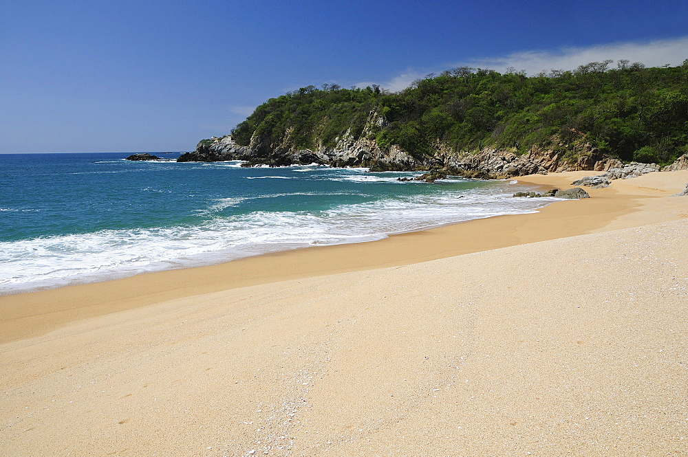 Mexico, Oaxaca, Huatulco, Playa Conejos Deserted beach with turquoise sea breaking on sandy shore and rocky headland.