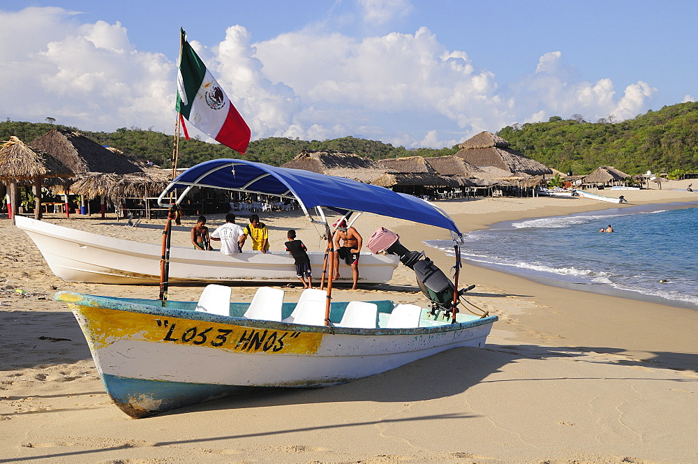 Mexico, Oaxaca, Huatulco, Fishing boats pulled up in front of beach shacks on Bahia San Agustin.