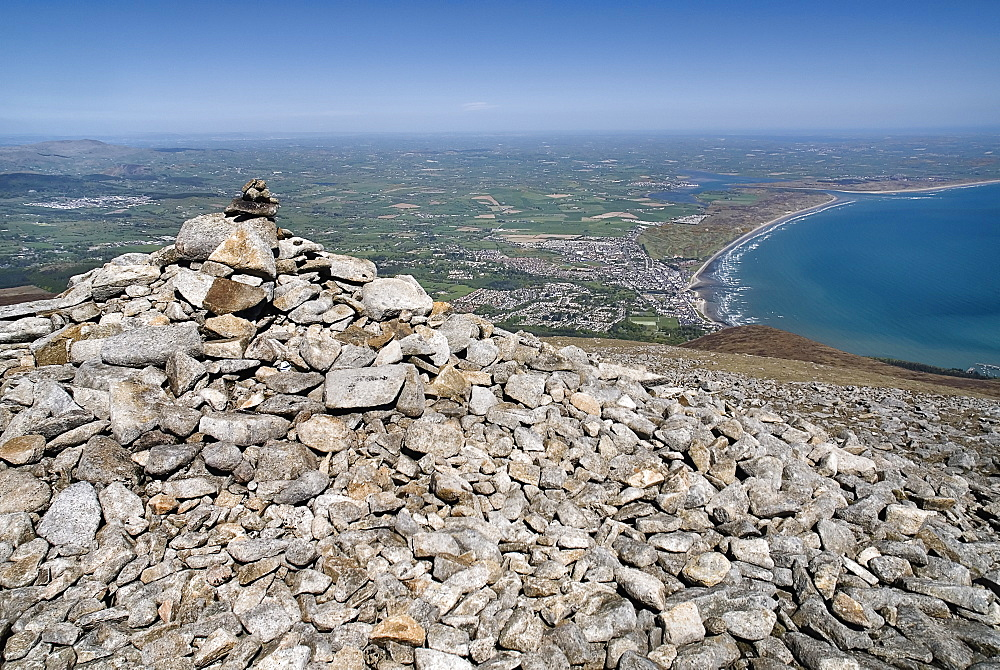 Ireland, County Down, Mourne Mountains, A cairn on the summit of Slieve Donard with Newcastle and its beach in the background