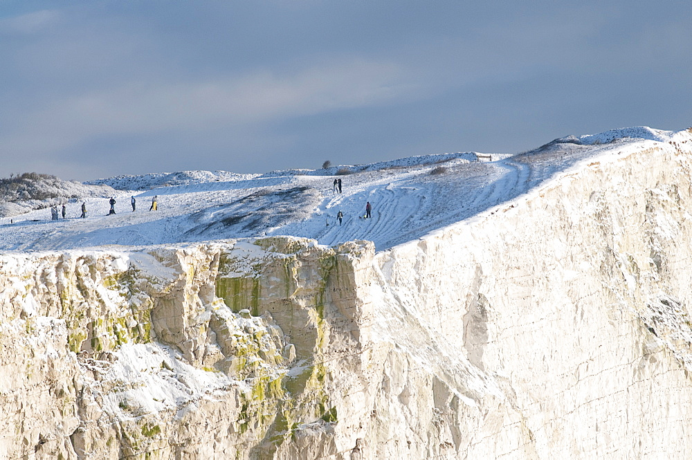 England, East Sussex, Seaford Head, Snow on cliffs with people toboganing.