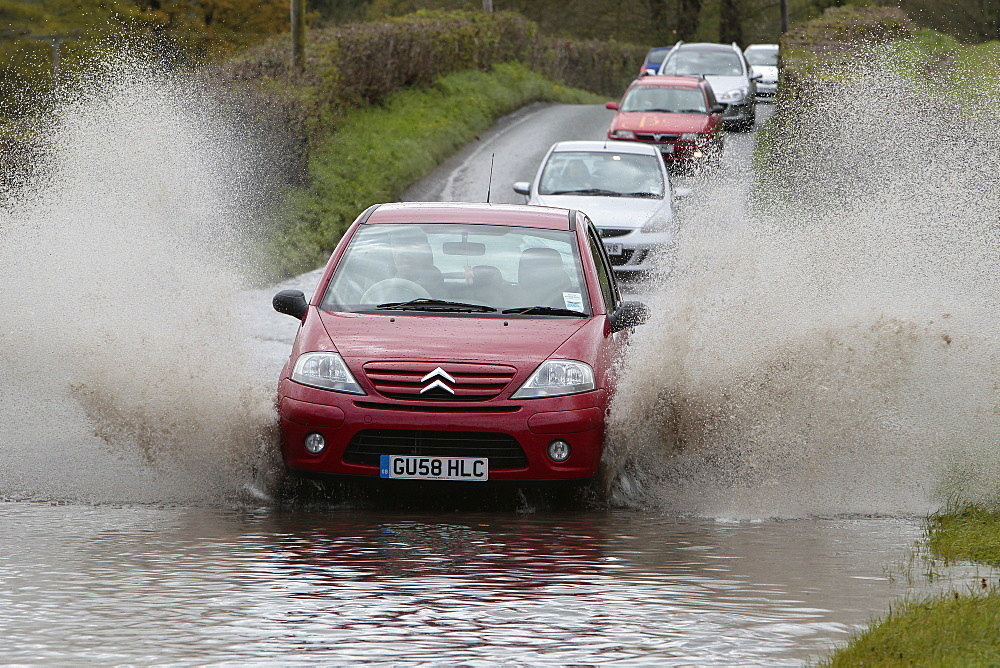 England, Kent, Flooding, Flooded country road with cars driving slowly through waters.