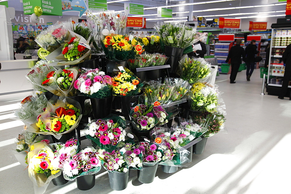 England, Shopping , Supermarket, Bunches of fresh flowers for sale by entrance.
