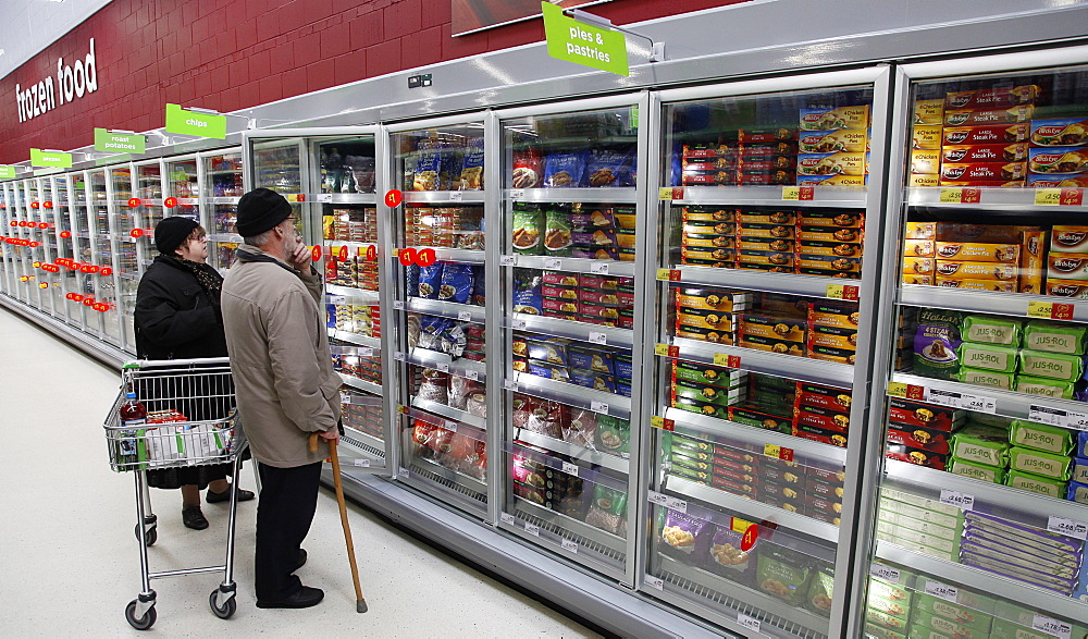 Shopping, Supermarket, Food, Elderly couple with shopping trolley looking at frozen goods in glass fronted freezer displays.
