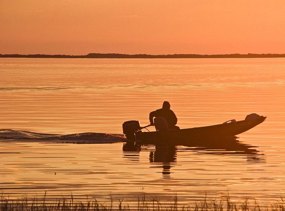 USA, Florida, Fisherman in his motorboat at Sunset.