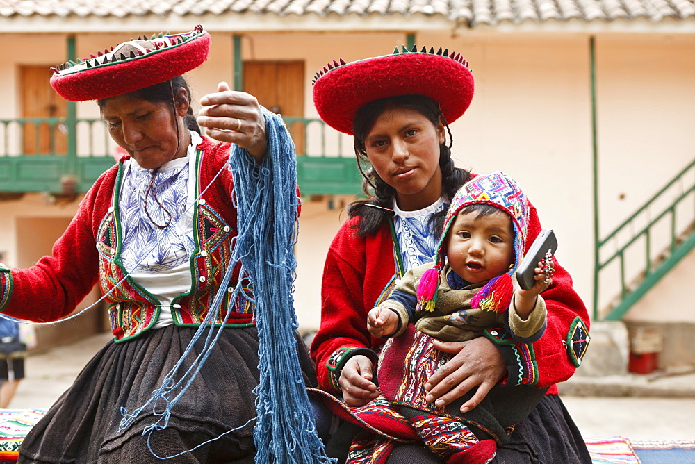 Peru, Indigenous People, Mother and baby in traditional dress with a lady making yarn and infant holding mobile phone.  - 797-10905