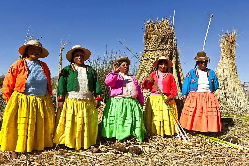 Peru, Puno, Lake Titicaca Women in colorful clothing on Grass Island.