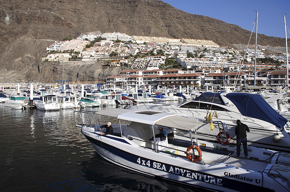 Spain, Canary Islands, Tenerife, Los Gigantes view across marina with boats moored.