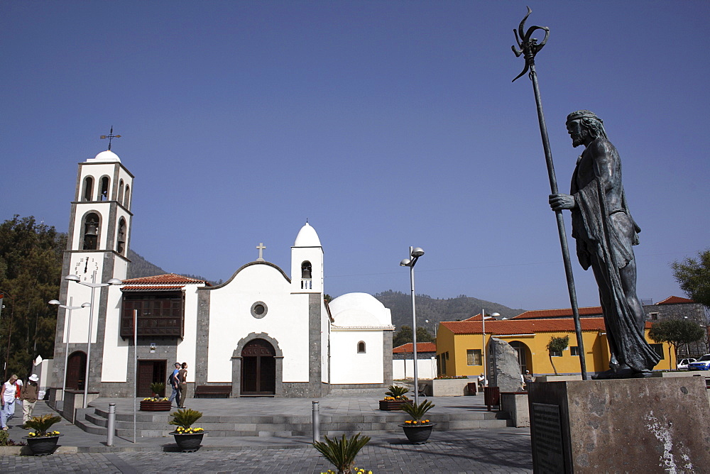 Spain, Canary Islands, Tenerife, Santiago del Teide Exterior of church with statue of Guanche chief in the foreground.