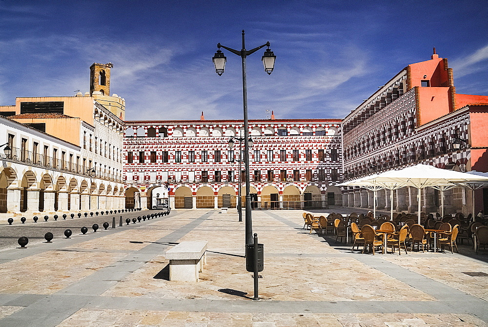 Spain, Extremadura, Badajoz, Colourfully painted buidlings in the Plaza Alta with Espantaperros tower behind.
