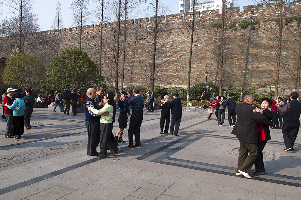 China, Jiangsu, Nanjing, Retired couples enjoying ballroom dancing beneath the old Ming city wall in Xuanwu Lake park with a modern skyscraper in the background.