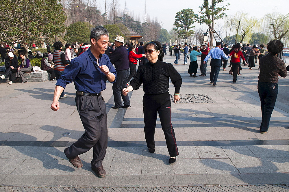 China, Jiangsu, Nanjing, Retired couples dancing beneath the Ming city wall at Xuanwu Lake Park Couple in foreground swinging arms in modern dance.
