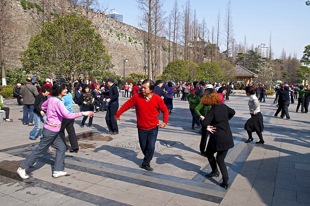 China, Jiangsu, Nanjing, Retired couples dancing beneath the Ming city wall at Xuanwu Lake Park Man in red sweater with arm extended to woman in pink sweater.