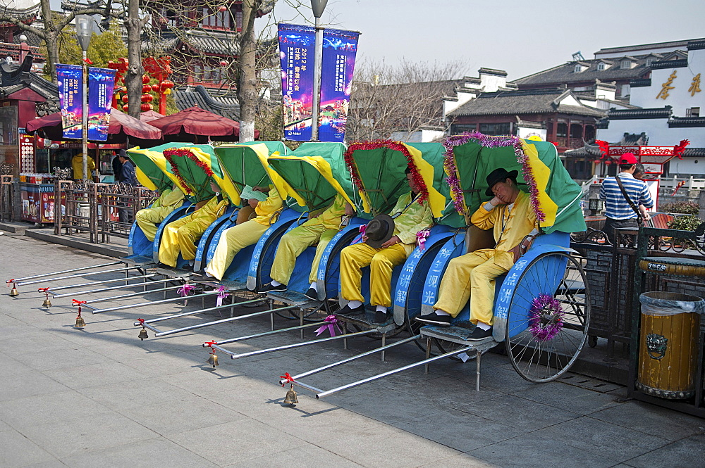 China, Jiangsu, Nanjing, Row of rickshaws with the rickshaw pullers in yellow uniform and hats asleep outside the Fuzi Temple a top tourist spot Fuzi Temple complex tile roofs and red Chinese lanterns in the background.