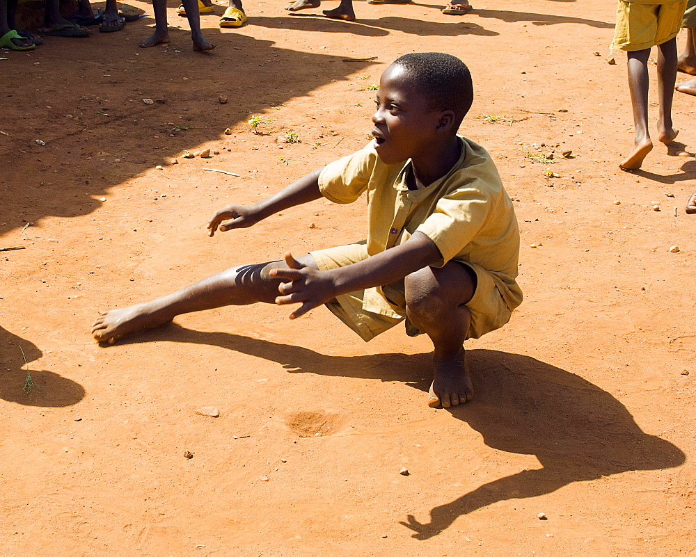 Burundi, Cibitoke Province, Buganda, Ruhagurika Primary School boys playing marbles during their playtime outside Ruhagurika Catch-Up Class. Catch up classes were established by Concern Worldwide across a number of schools in Cibitoke to provide a second chance for children who had dropped out.