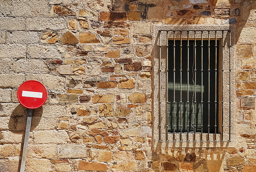 Spain, Extremadura, Caceres, No Entry sign against typical brick wall.
