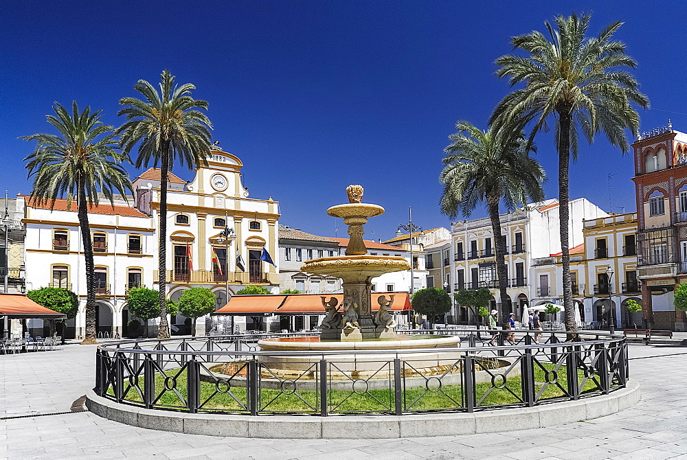 Spain, Extremadura, Merida, Plaza de Espana with fountain and palm trees.