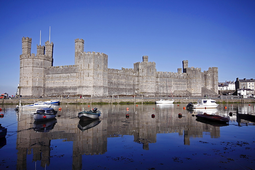 Wales, Gwynedd, Caernarfon, Caernarfon Castle Against Deep Blue Sky Overlooking The River Seiont as the tide comes in Construction Started In 1283 And Prince Charles Held His Investiture At The Castle In 1969. A UNESCO World