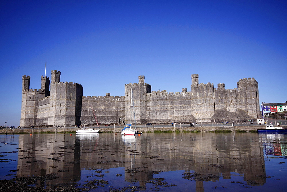 Wales, Gwynedd, Caernarfon, Caernarfon Castle Against Deep Blue Sky Overlooking The River Seiont as the tide comes in Construction Started In 1283 And Prince Charles Held His Investiture At The Castle In 1969. A UNESCO World Heritage Site.
