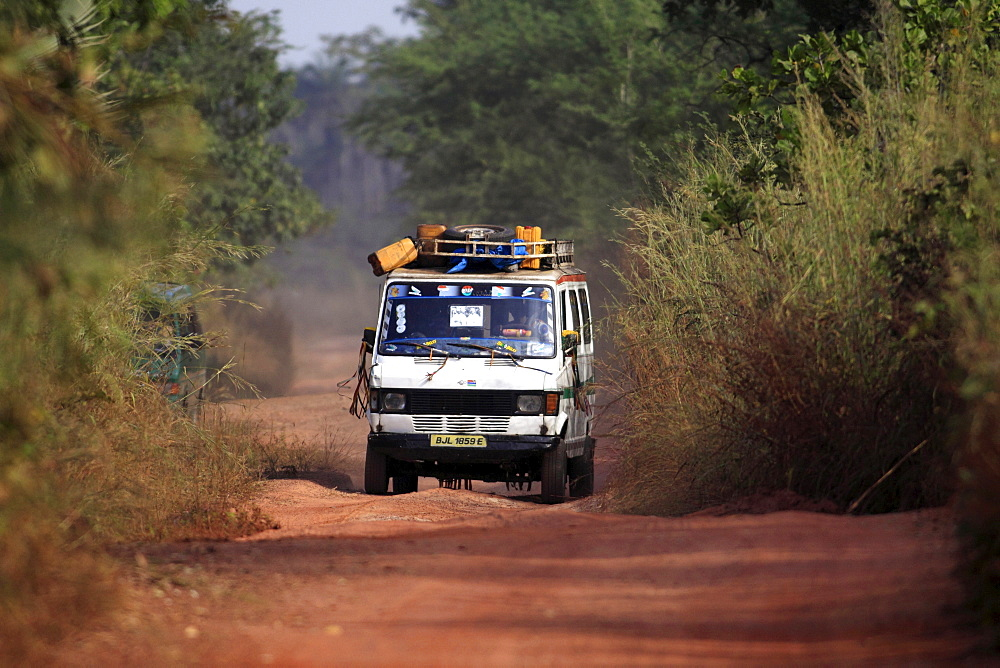 Gambia, Transport, Minibus driving down narrow dirt road covered in red soil carrying provisions on roof rack.