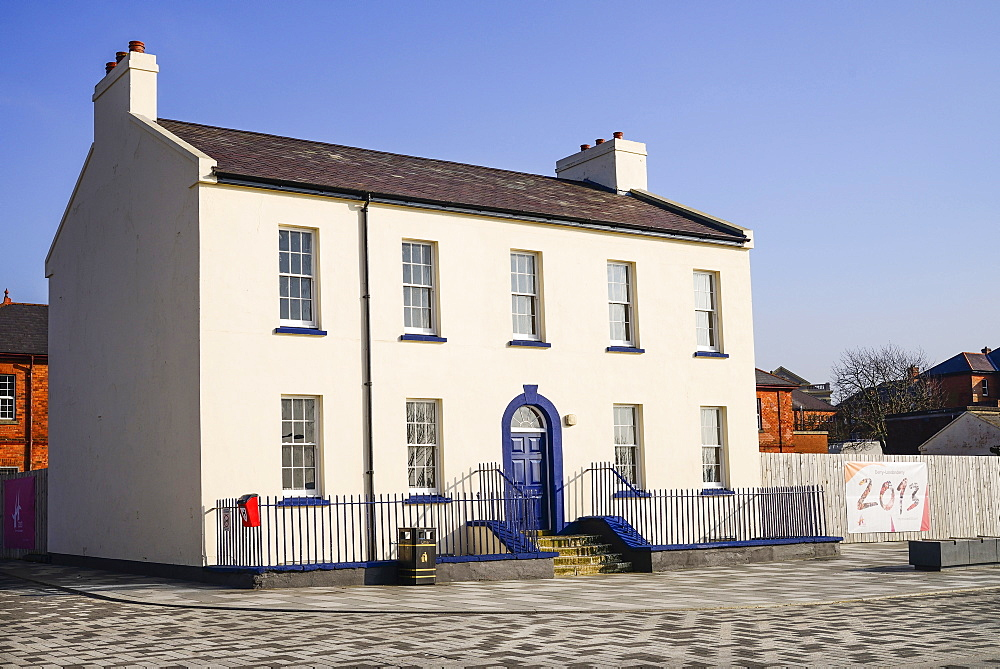 Ireland, North, Derry, Former Ebrington Barracks building with blue doorway and small Derry 2013 Year of Culture banner.