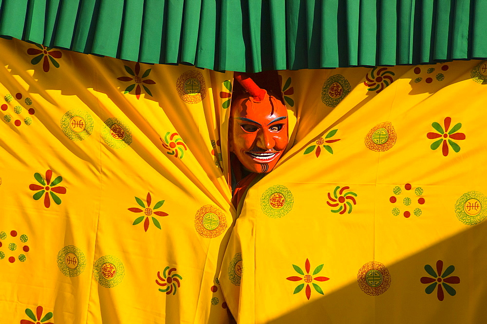 Bhutan, Thimpu Dzong, Atsara, or comedian peering out from behind a curtain at a masked dance Tsecchu.
