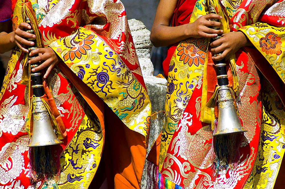 Bhutan, Bumthang District, Tamshing Lhakang, Buddhist pipe players dressed in ceremonial silk robes.