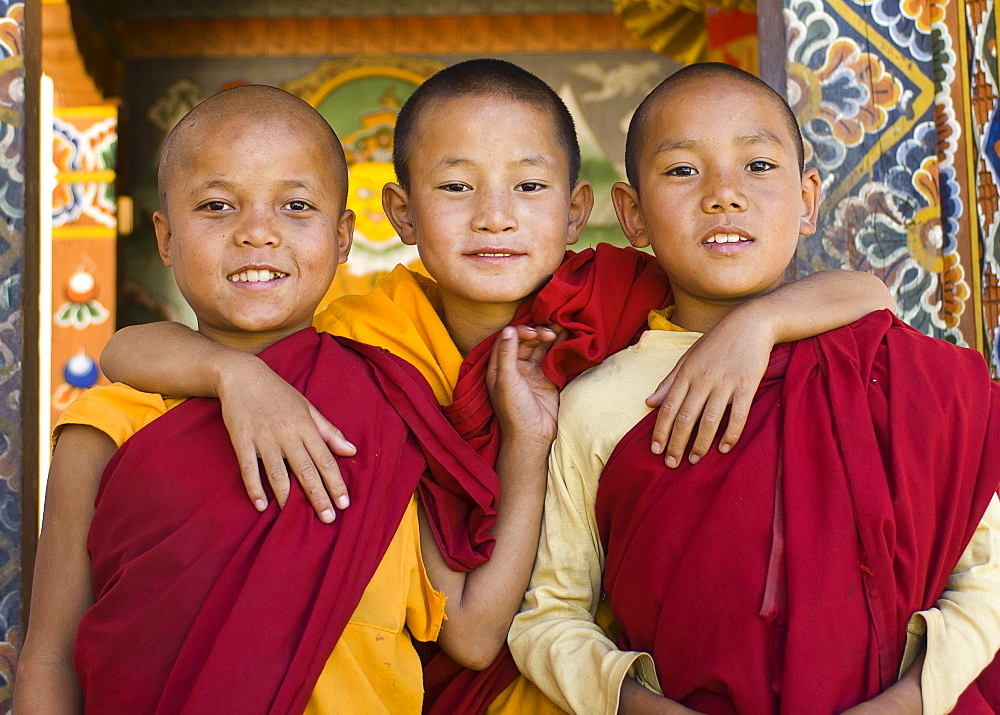 Bhutan, Punakha, Three young novice monks standing in doorway of Chimi Lakhang temple in the old capital. - 797-11466