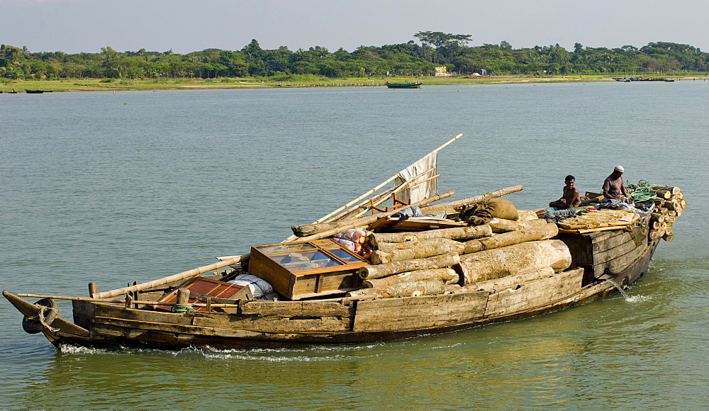 Bangladesh, Industry, Transport, Boat heavily laden with cargo of timber and furniture on river.