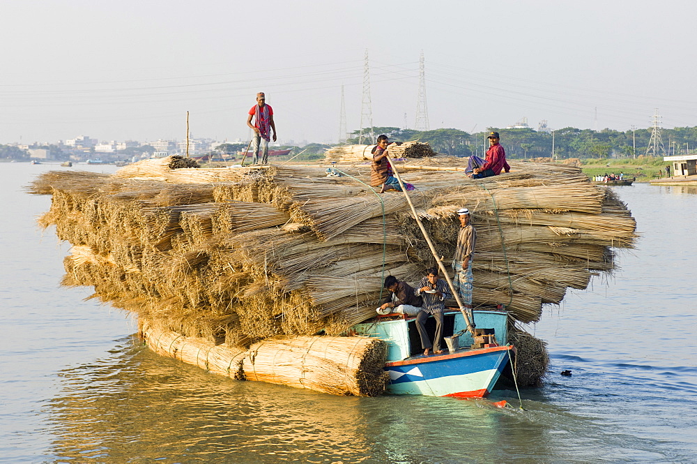 Bangladesh, Industry, Transport, Boat heavily laden with a cargo of jute stems on river.
