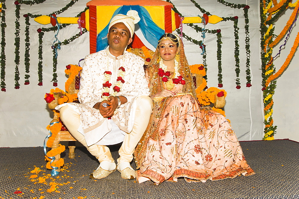 Bangladesh, Dahka, Bride and groom dressed up in glitzy jewellery and flowers for their wedding.