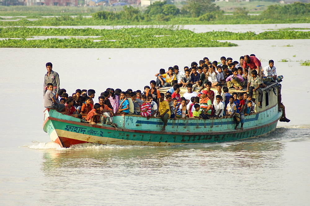 Bangladesh, Dhaka Division, Keraniganj Upazila, Overcrowded boat travelling down a tributary river.,